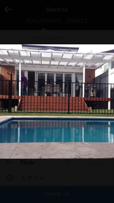 View from pool leading to deck and into the house