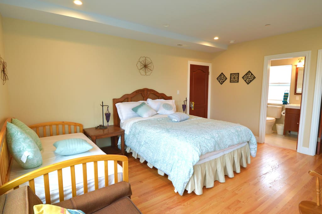 The bedroom with one queen bed, one single bed, and an expandable sofa bed