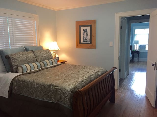 Queen size bed and closet with shelf storage and clothes rack.