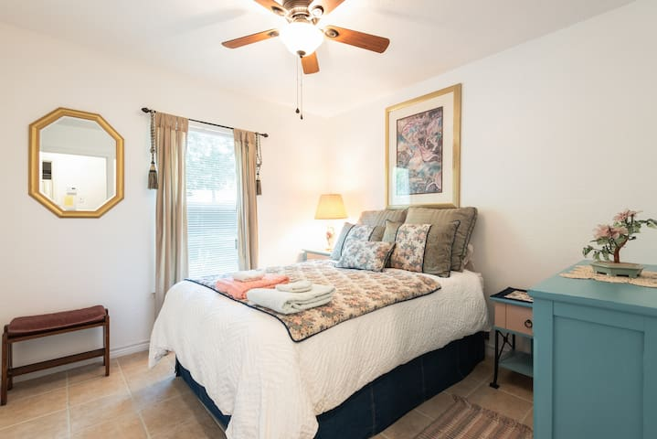 This country style bedroom displays a double bed covered in tapestry and denim complimented by matching end table and chest of drawers accented by magical metallic carousel horses.