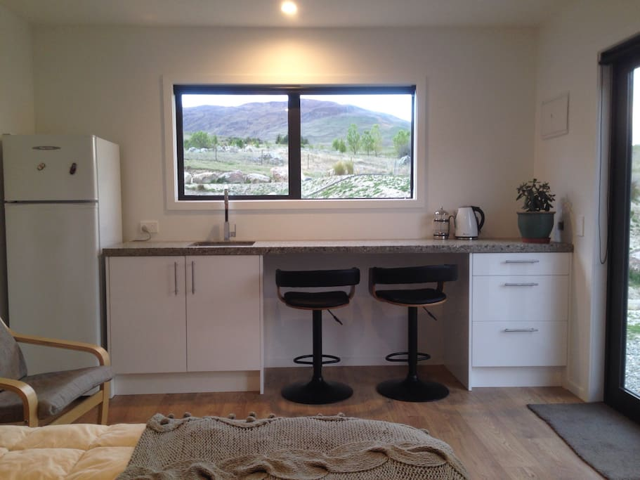 Modern kitchen area - includes kettle, toaster, induction stove top, conventional oven/microwave/grill, fridge & freezer.