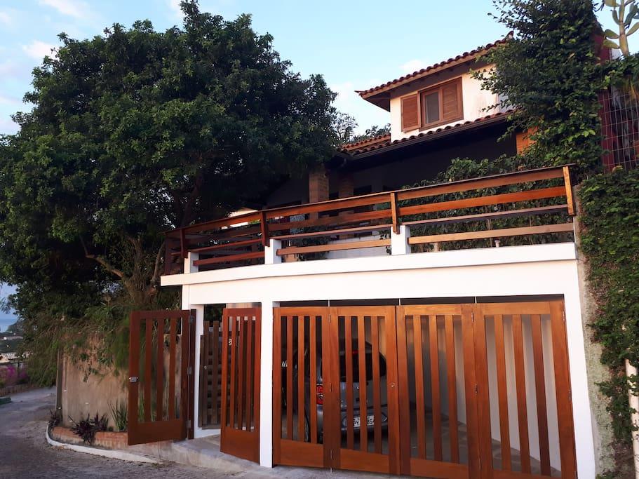 Frente da casa, com garagem, portão de entrada, acesso principal ao terraço, acesso principal à varanda e à casa.