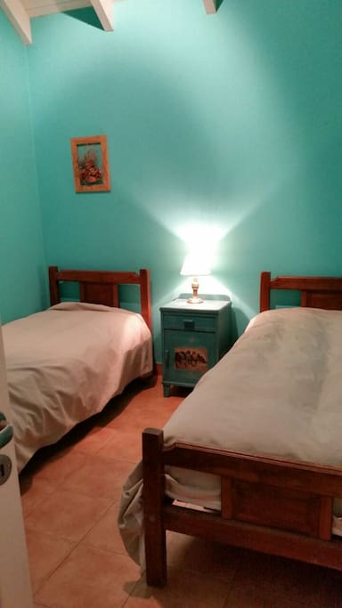 Habitación con dos camas individuales , placard y cajonera.