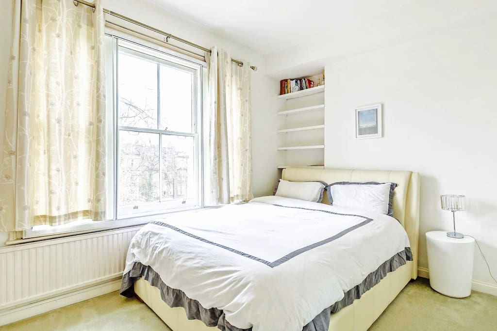 Spacious master bedroom with king sized bed, large built-in wardrobe, dressing table and large windows overlooking a lovely garden.