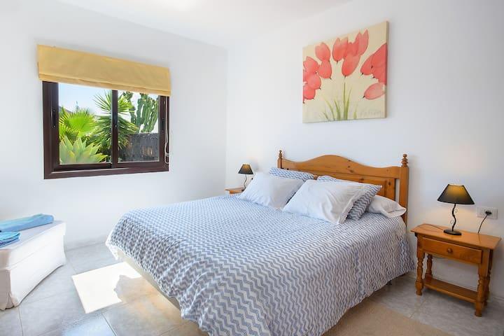 dormitorio principal con cama extra grande y vistas al jardin,donde podran disfrutar de un bonito amanecer.