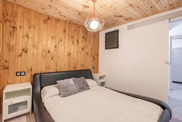 Habitacion de matrimonio con frontal  y techo de madera natural ,cama de 150x200 con colchon terapeutico de alta calidad, dos mesitas de noche con enchufes cercanos y television de pantalla plana.