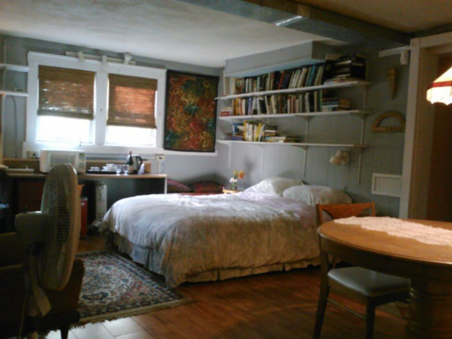 Queen bed and books. The room features a mini fridge, microwave oven, and electric tea kettle.
