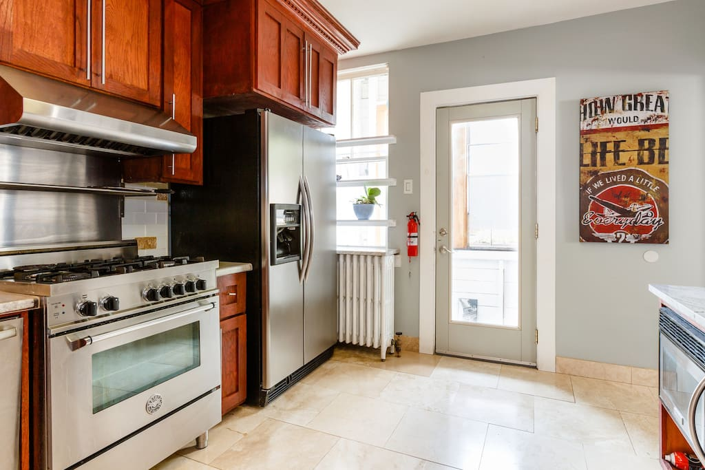 Kitchen with professional gas stove, filtered water and ice maker on the front of the refrigerator