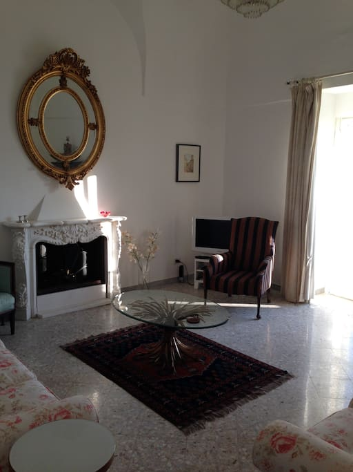 Morning sun in the comfortable, spacious sitting-room with balcony, fireplace, high ceilings and wonderful view.