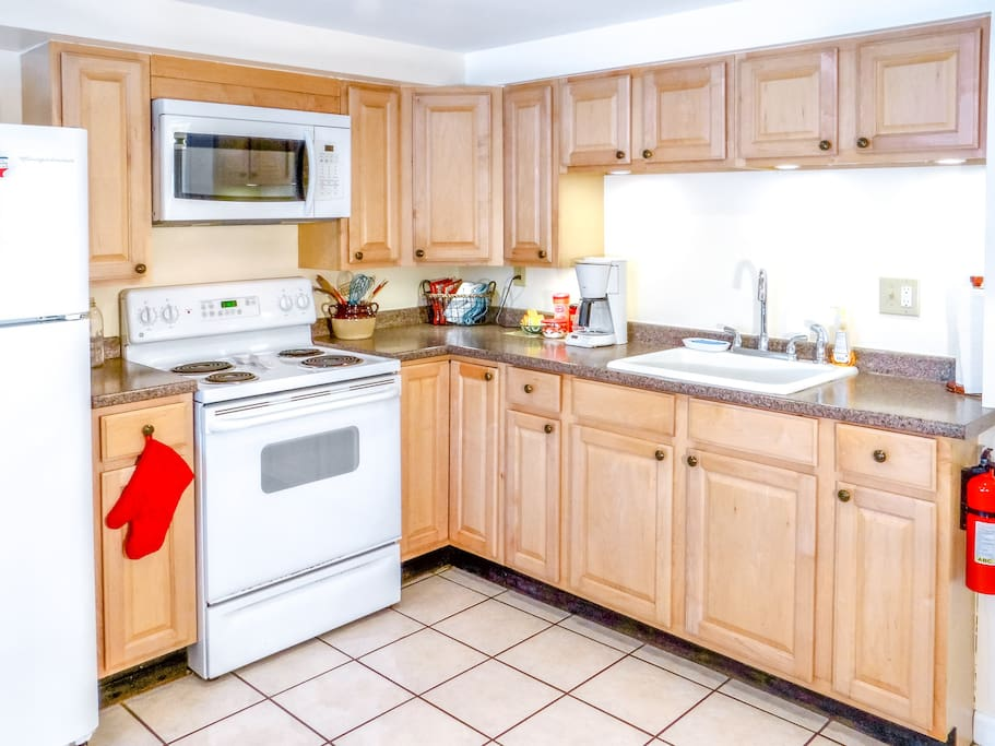 Bright full kitchen with microwave and coffee maker.