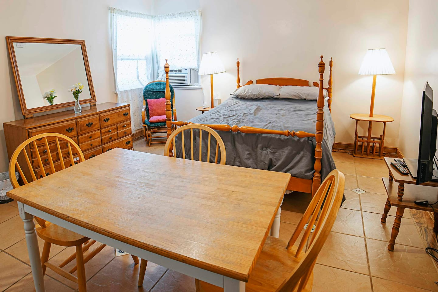 Bedroom offers full size bed, dresser, dining table, TV, cooking corner, heating and air conditioning.