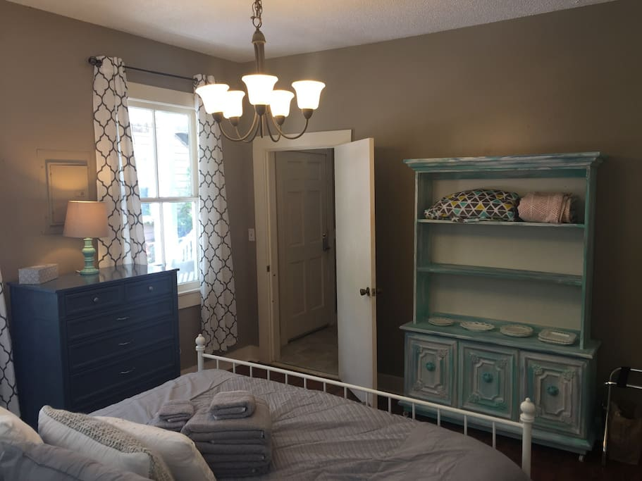 This is our master bedroom, looking out into the rest of the apartment. Sleep on a comfortable queen bed and experience a true Charleston single house.