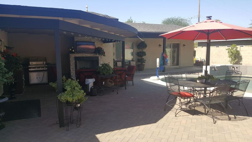 Shared courtyard with outdoor living room, fireplace, TV, barbecue, seating area, dining table, pool, and sun lounges