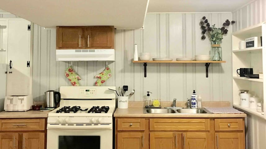 Double sink, pots and pans available, and stoneware dinner set.