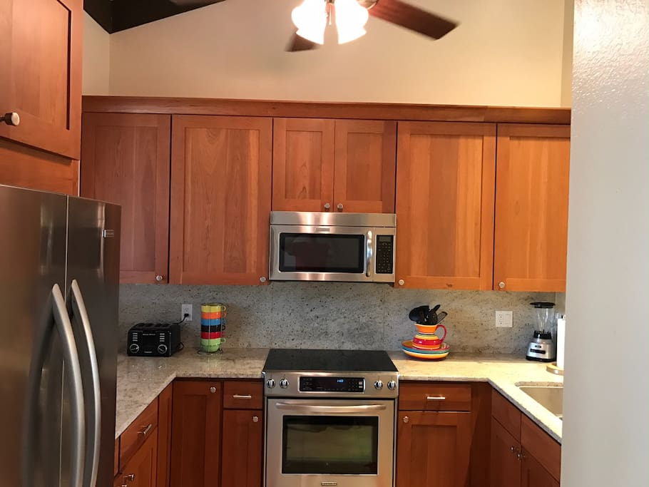 New kitchen with upgraded appliances and granite counters, pretty dishes and everything you need