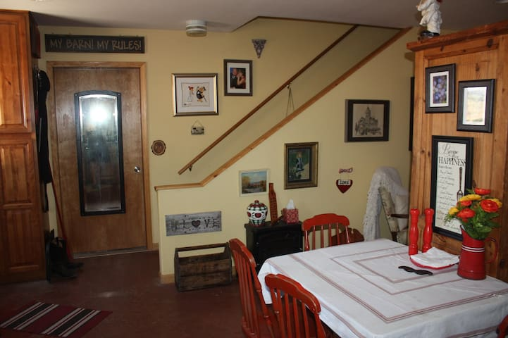 View of kitchen dining space and stairs to loft area. Additional patio table for outdoor use is available to guests as well.