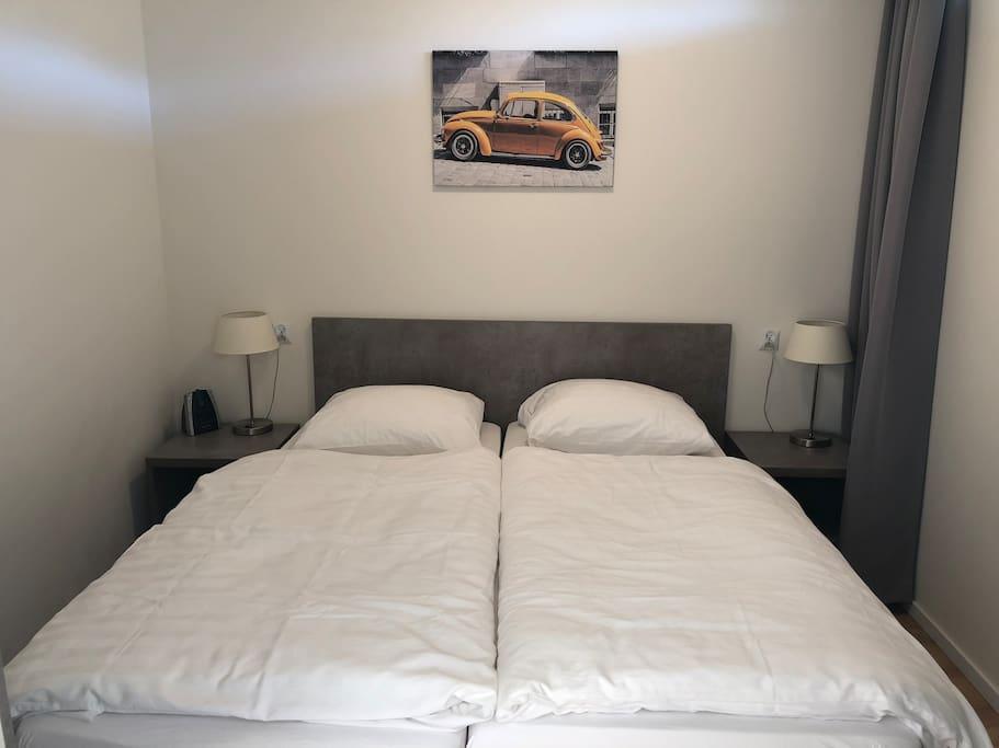 Slaapkamer met een kledingkast en een extra stoel.