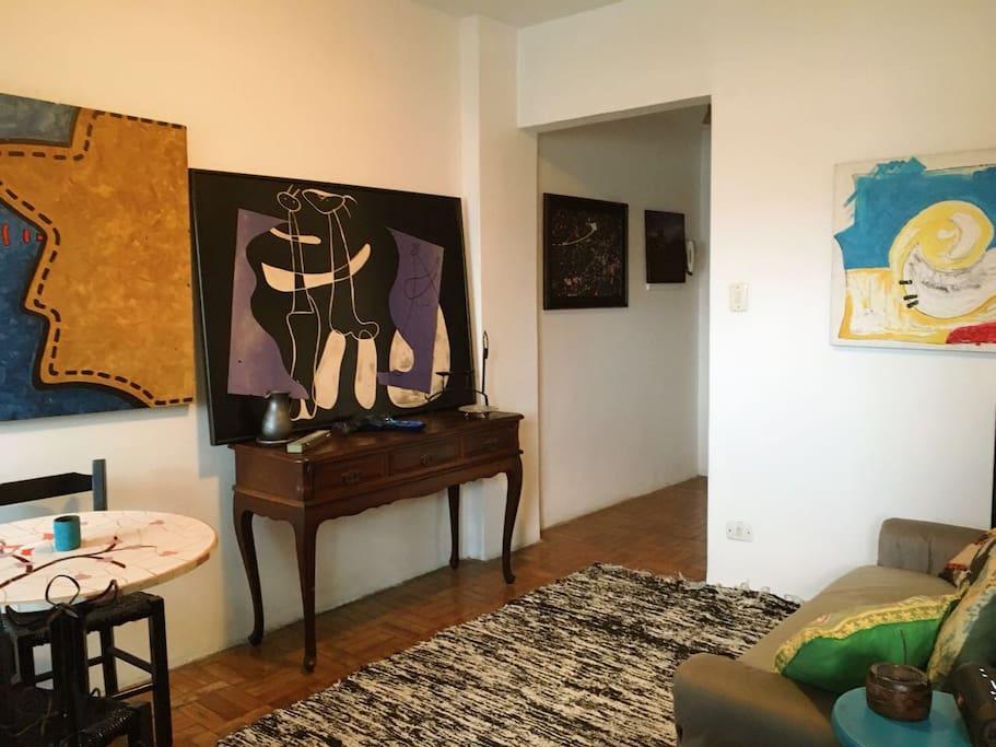Sala de estar confortável com sofá cama, mesa, aparador e muita arte para encantar e agradar os olhos e o coração.
