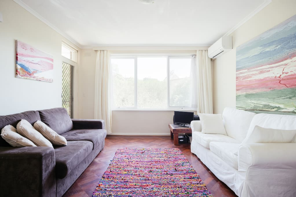 Cosy couches and cottonspun rug on parquetry floor
