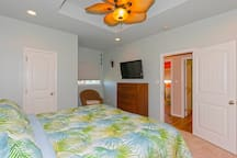 The master bedroom has a king sized bed and coastal decor