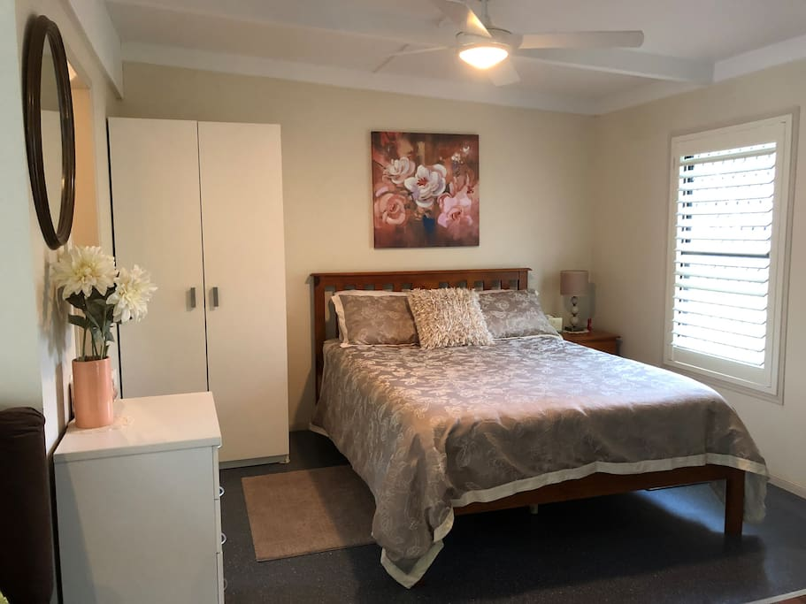 Queen size bed in the spacious bedroom. New plantation shutters adding more comfort and privacy.