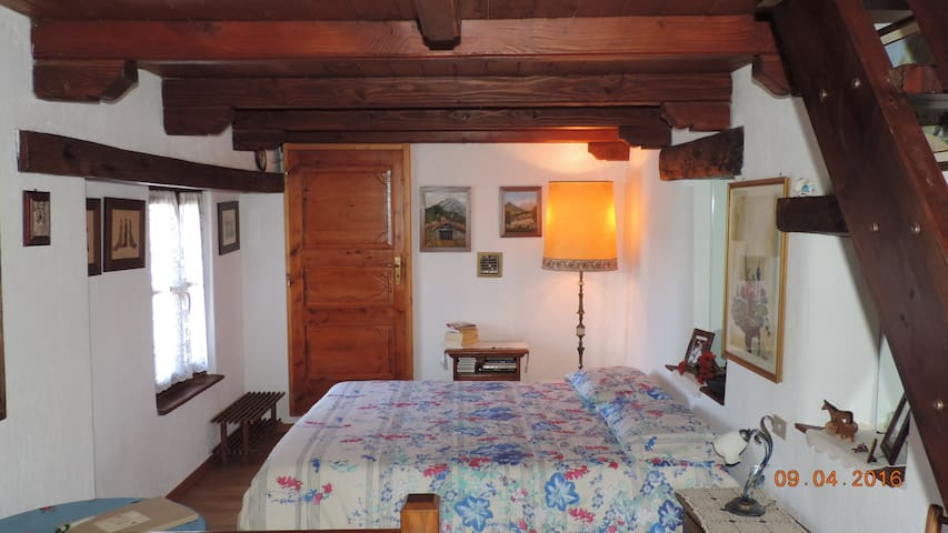 La camera matrimoniale al 1° livello - The master bedroom on the first level with wooden floor and ceiling