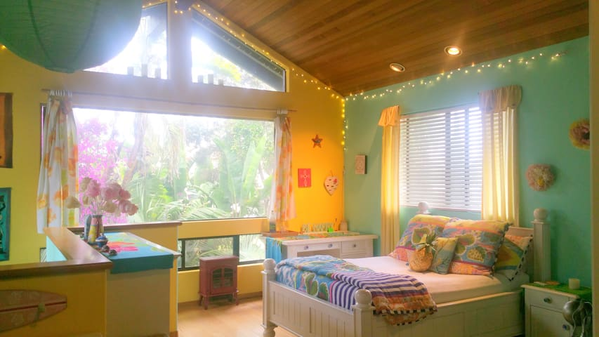 South Pacific in-suite bedroom with full-size bed, hardwood floors, desk with high-speed WiFi, and redwood ceiling.