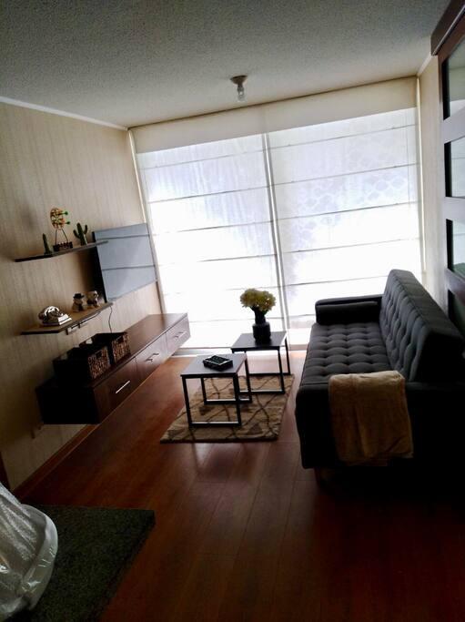 Sala del departamento con los estores cerrados hacia el balcón