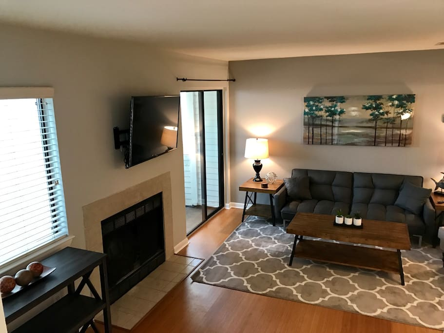 Living Room area with 48'' smart TV with Netflix, Hulu, Amazon, and Pandora. Sliding door opens to outdoor screened in patio.
