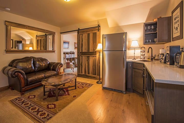 Living room and kitchenette. The kitchenette is outfitted with a refrigerator/freezer, microwave, two burner stove, toaster oven, electric kettle, french press, standard cooking utensils, full sets of dishes/glasses/wine glasses, and an outside BBQ.