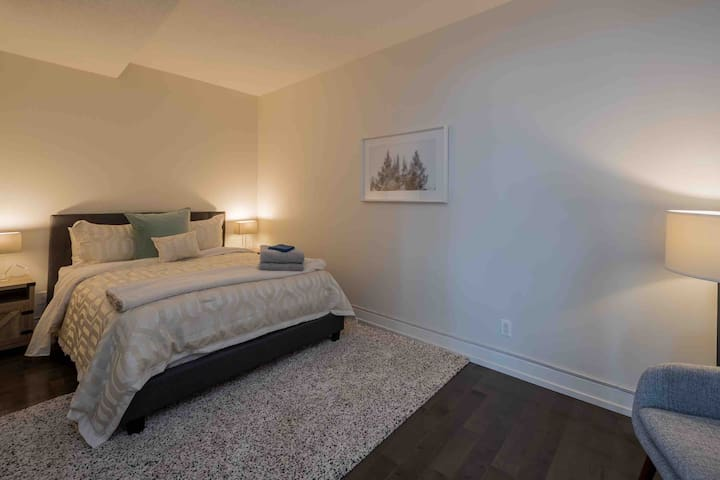 This bedroom is spacious and luxurious, a queen bed and plush rug. It has no windows but light passes through the frosted glass double doors.