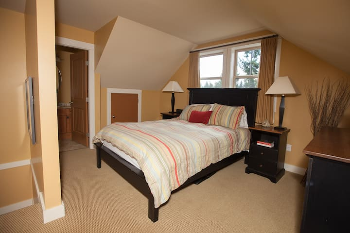 The loft style bedroom with a comfy queen sized bed and attached 2nd bathroom.