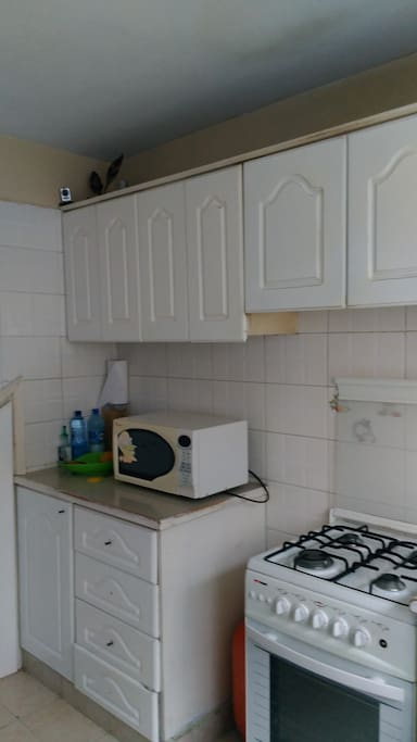 Kitchen equipped with microwave,cooker,sandwich maker,kettle ,blender,rice maker and fridge.