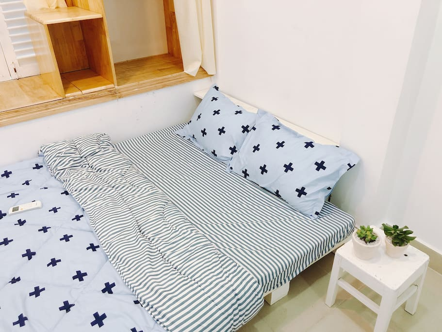 A double sized bed in a cozy private room with a bedside table