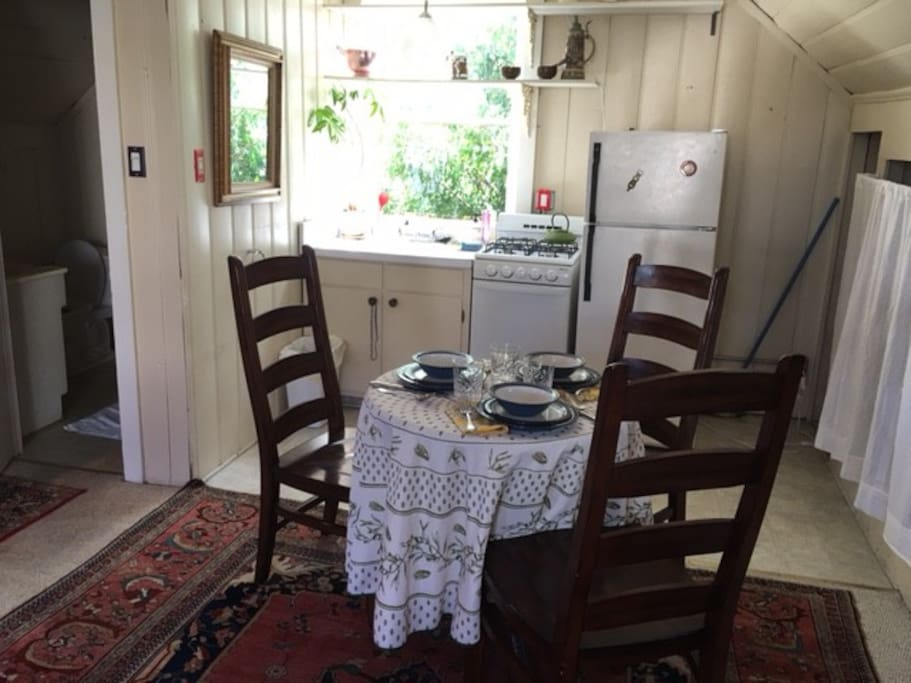 Small stove, fridge, oven, microwave and table settings for three