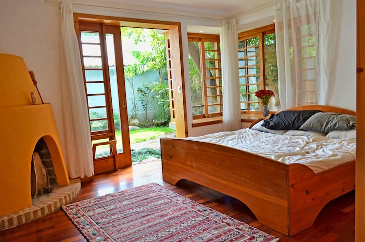 Large master bedroom with king bed, fireplace, door to garden, closet space and large windows with screens