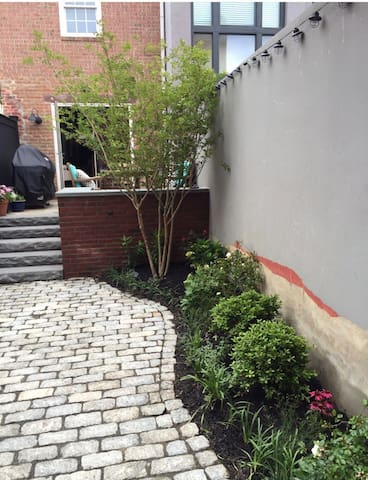 Step down to the garden/patio area that doubles as a private parking space