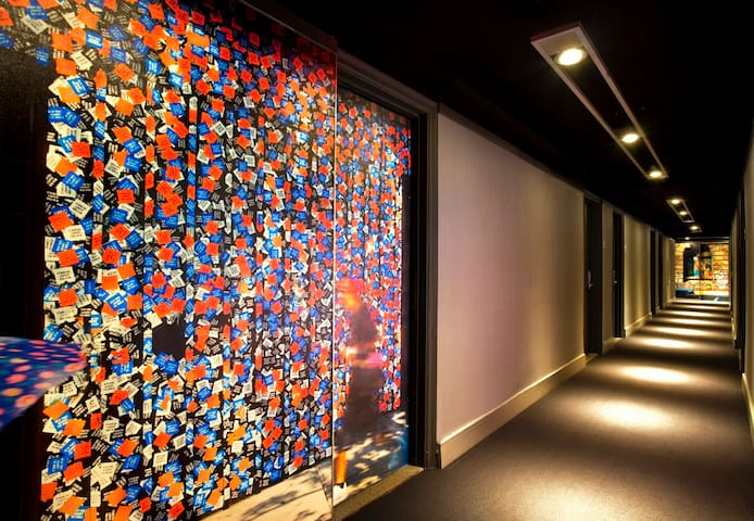Bold graphic wall coverings reference the bright lights and signage of Broadway.