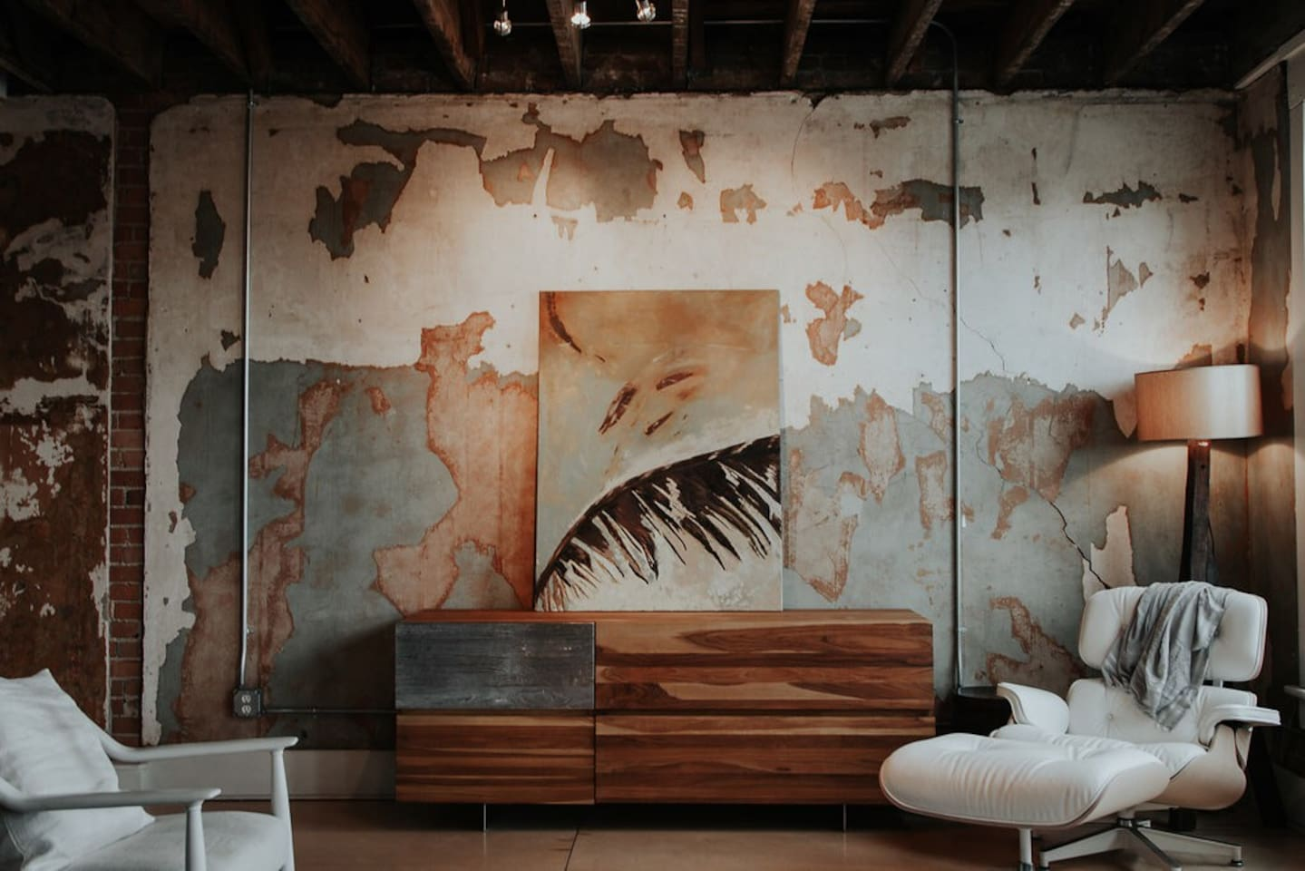 Gorgeous, natural light filled living room featuring remnants of original decor, a view of historic downtown Benton Harbor, and chic retro-cool furniture.