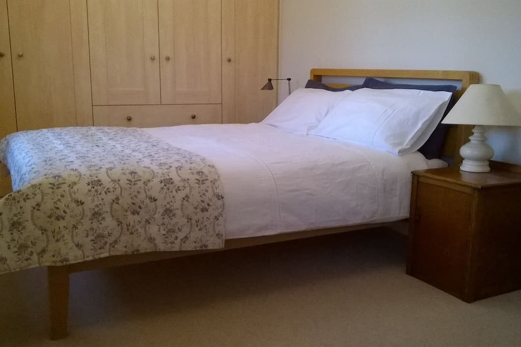 Comfortable double bed with bedside lights on either side; ample wardrobes; desk; TV