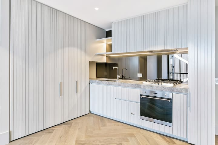 Kitchen with dishes, cutlery, pots, pans, fridge, cabinets, kettle, essential condiments.