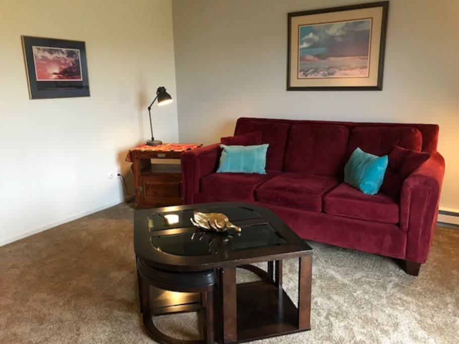 Spacious living room with couch, recliner, TV with cable and coffee table.  Sliding glass door leads out to the patio overlooking yard and pasture.