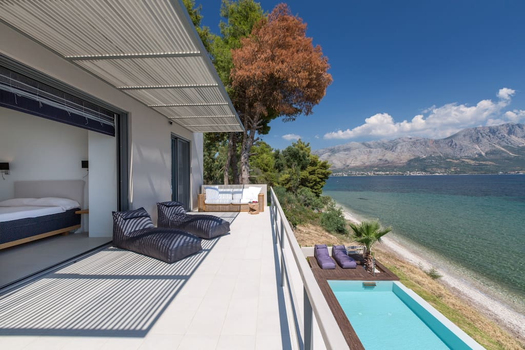 French doors open the full length of the bedrooms onto a balcony that has loungers and seating. Stunning views over the bay