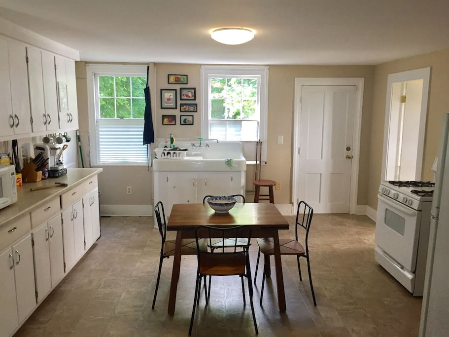 Eat-in kitchen with microwave, oven, toaster, full size refrigerator and freezer, and original porcelain farm sink.