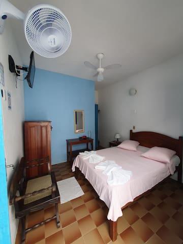 Um apartamento com 1 cama de casal com toalhas e roupa de cama, 2 vetiladores, 1 televisão, Internet Wi-Fi, secador e 1 cômoda.