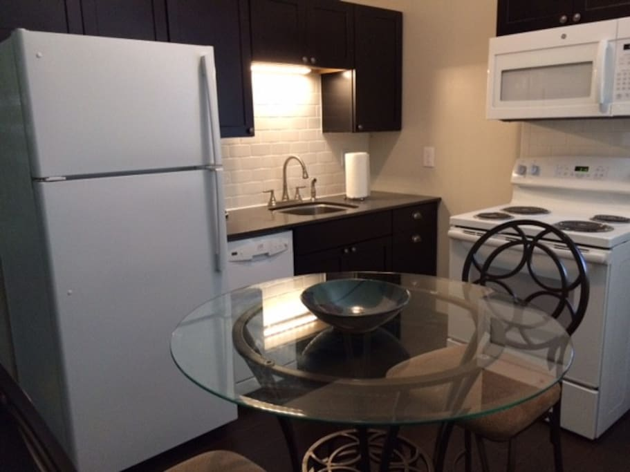 Fully functioning Kitchen with full size frig, stove, dishwasher and microwave solid surface countertop large stainless sink