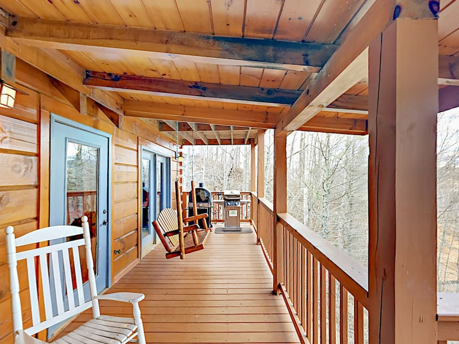 Upper deck with porch swing, rocking chair, gas grill, and pizza oven.