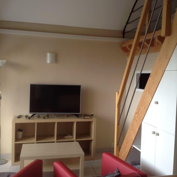télé et escalier menant à 2 chambres en mezzanine