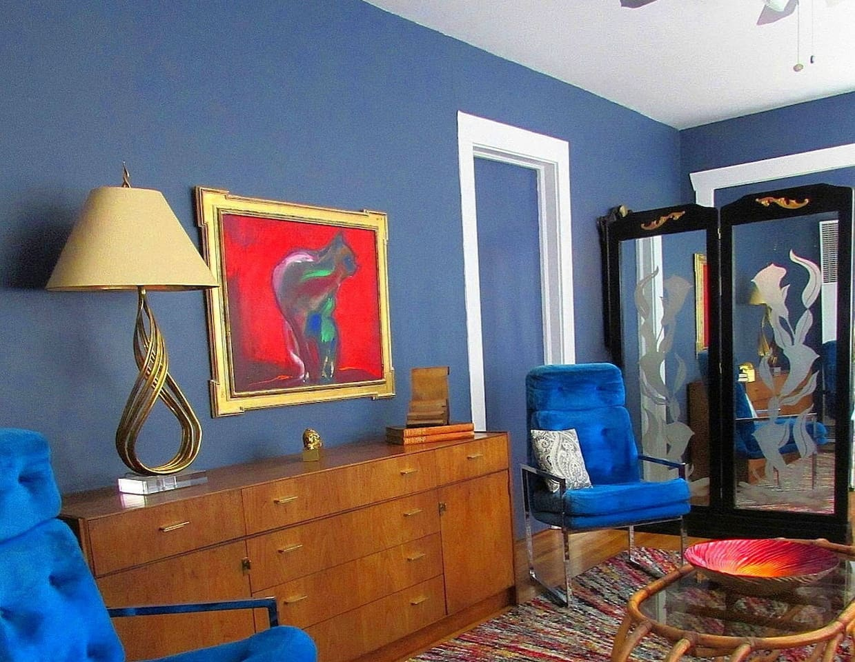 A vintage brass lamp, dynamite cat painting and mirrored, frosted glass screen outfit the comfortable living room.