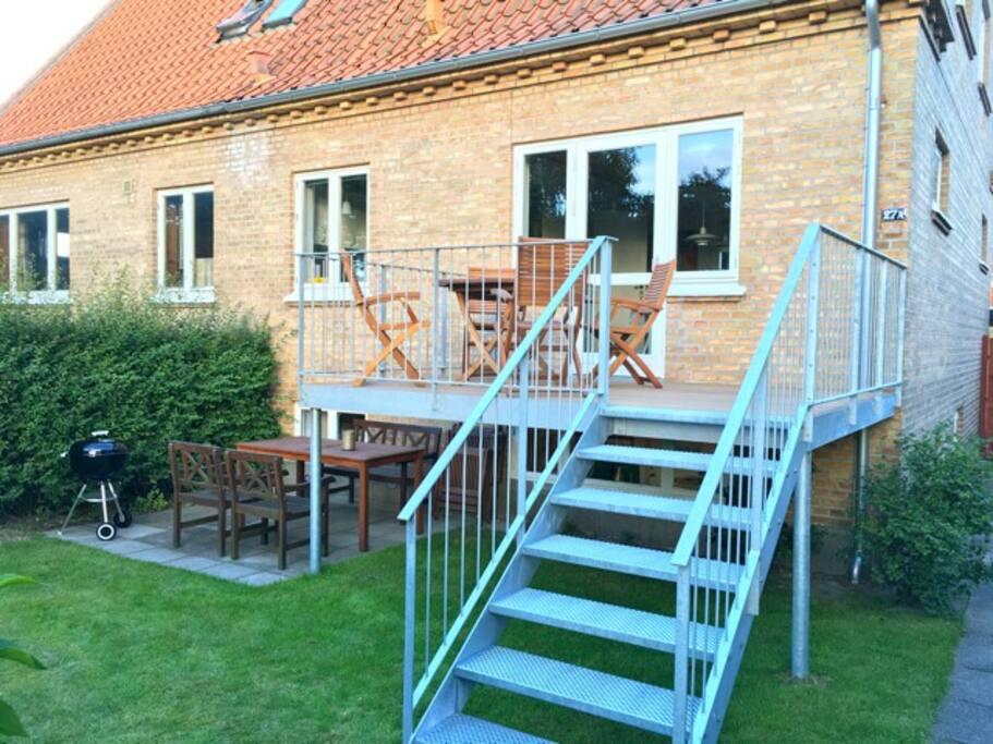 Forhave med balkon, terrasse med grill og græsplæne